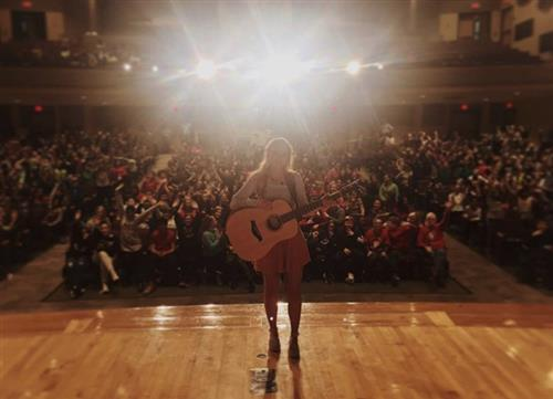 Jessie Chris on stage in packed Franklin Middle auditorium