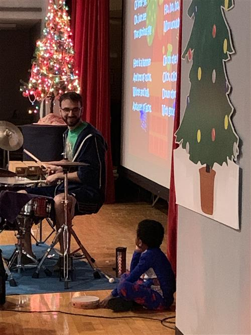 Noah Fuchs plays the drums as student looks on