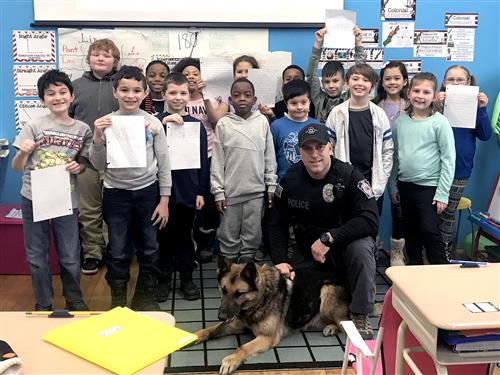 Officer Costello and Tank pose with class