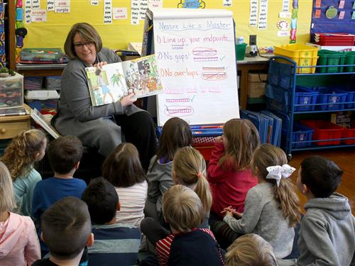 Assistant Superintendent Kelly White reading to students