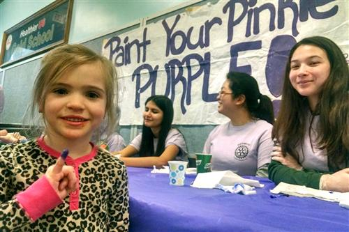 Students have their pinkies painted purple