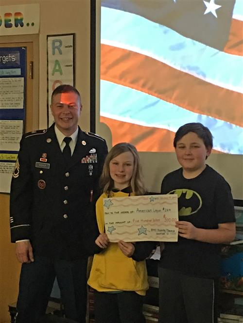 Students Emma Piadlo and William Nowak presenting First Sergeant Trudeau
