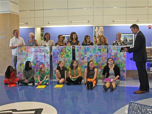 Students & teachers with artwork in the background
