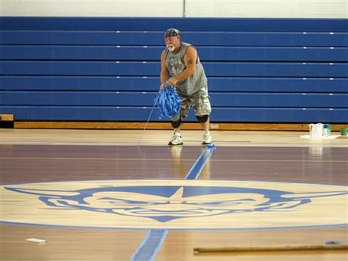 Worker removes tape from gym floor