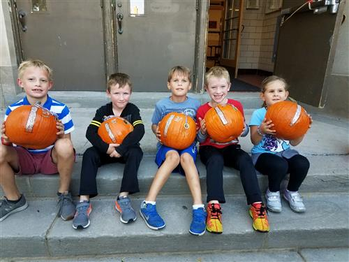 Students holding pumpkins