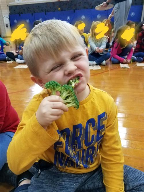 Student eating broccoli