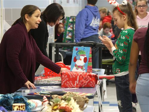 Kenmore West staff wrap a student's gift at holiday shop during lunch