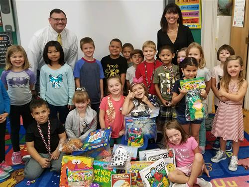 Teacher Katie Sacco & Principal David King pose with students and games/activities