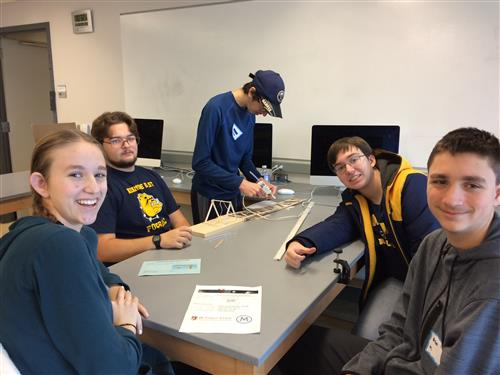 Kenmore East Physics Olympics competitor taking part in Craft Stick Crane event