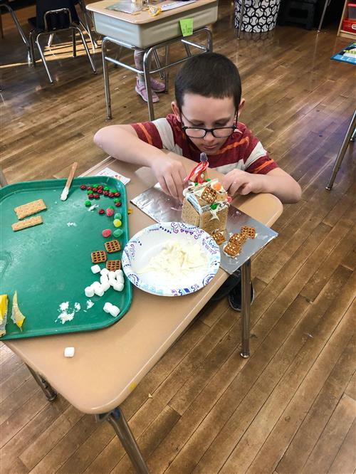 Student works on gingerbread house creation