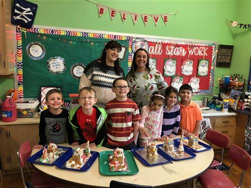 Students/staff pose with gingerbread house creations