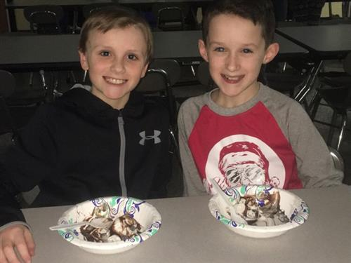 2 students smiling with bowls of ice cream