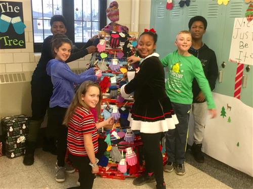 Students stand beside mitten tree